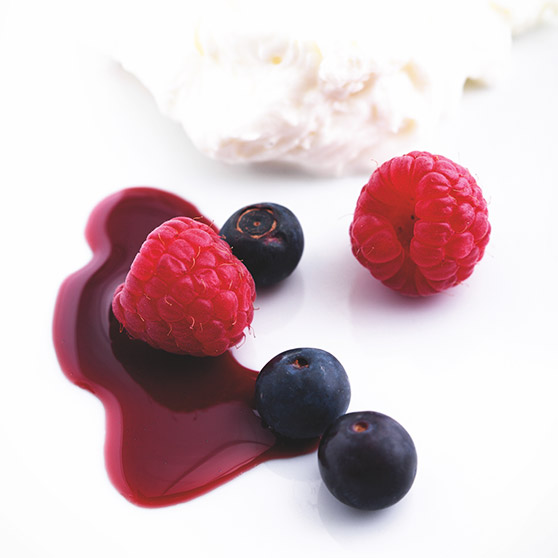 Yoghurt dessert with red wine coulis and berries